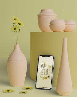 Mock-up vasi 3d per fiori con dispositivo mobile