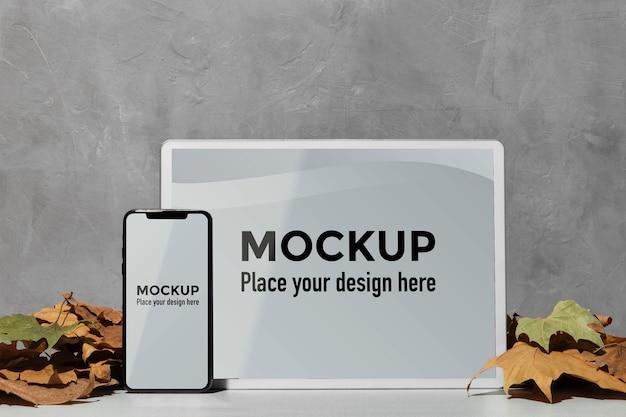 Mockup-apparaten die naast bladeren op de tafel staan