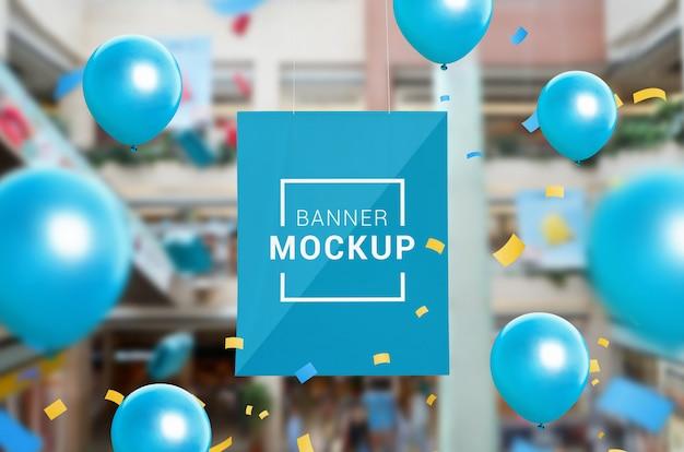 Mockup banner impiccato all'interno del centro commerciale. circondato da coriandoli e palloncini. promozione delle vendite