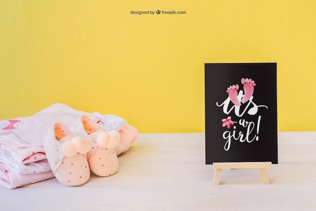 Mockup de bebé chica con tabla y zapatos