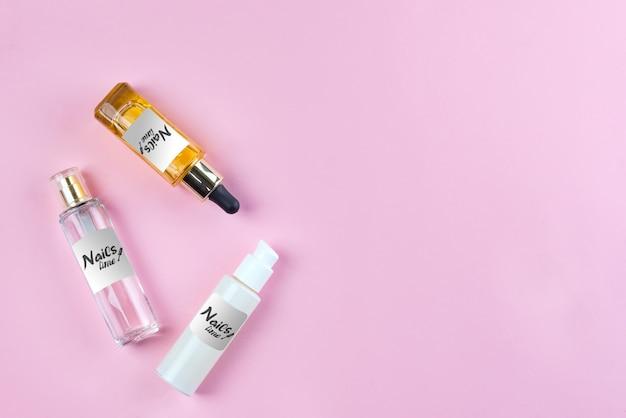 Mockup bottiglie e vasetti con cosmetici, creme e oli naturali per la cura della pelle su sfondo rosa.