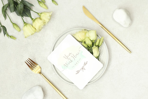 Mockup bruiloft kaart met bloemen en gouden bestek