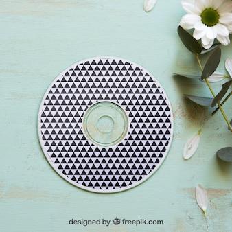 Mockup cd accanto al fiore