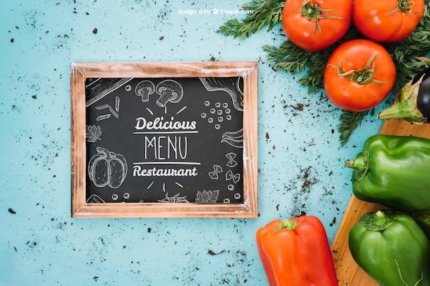 Mockup de comida vegetariana con pizarra a la izquierda
