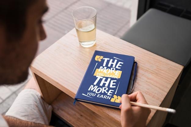 Mockup de cover de libro enfrente de hombre joven