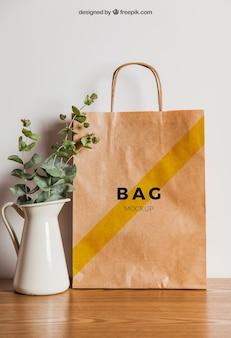 Mockup del sacchetto di carta e vaso di fiore