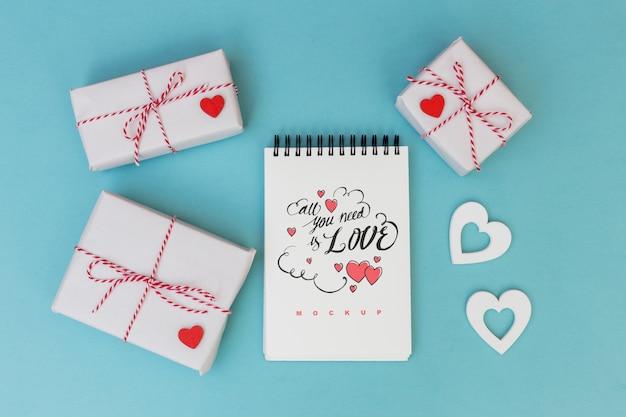 Mockup di blocco note accanto a scatole regalo per san valentino