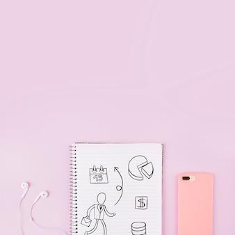 Mockup di blocco note accanto a smartphone e auricolari