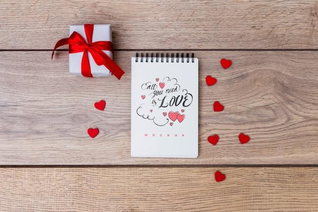 Mockup di blocco note accanto alla confezione regalo per san valentino