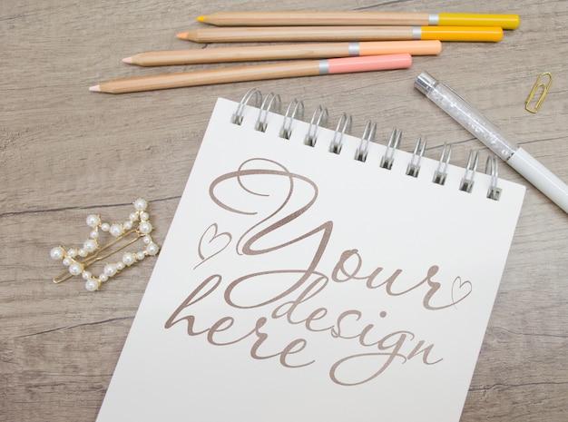 Mockup di blocco note con matite colorate