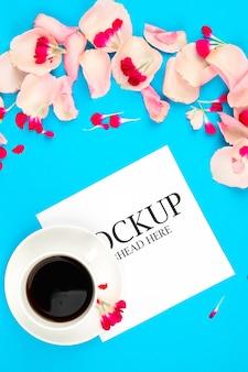 Mockup di carta bianca tazza di caffè e fiori rosa su sfondo blu