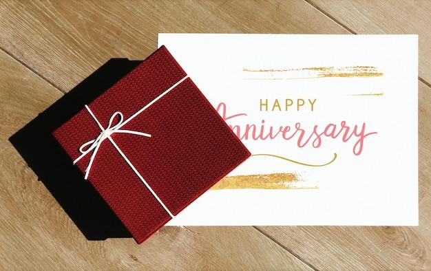Mockup di carta di anniversario felice con una scatola regalo