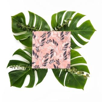 Mockup di carta quadrata con foglie tropicali
