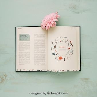 Mockup di concetto di primavera con libro e fiore rosa