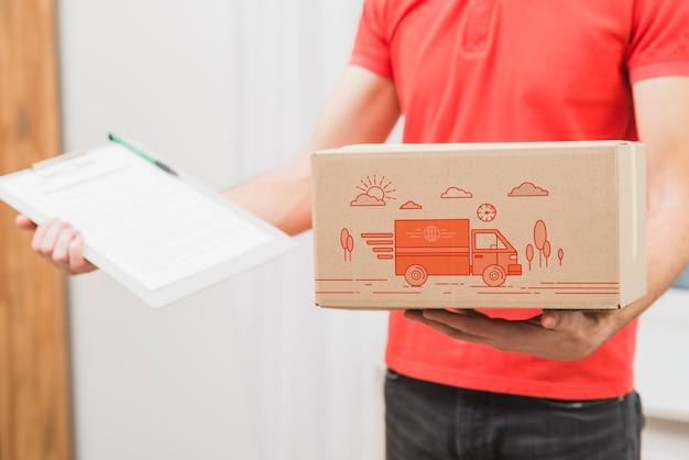 Mockup di consegna con la scatola della tenuta dell'uomo e la lavagna per appunti
