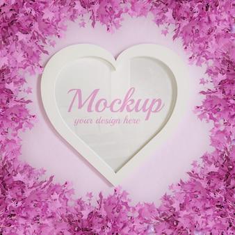 Mockup di cornice a forma di cuore incorniciato da piante a foglia rosa