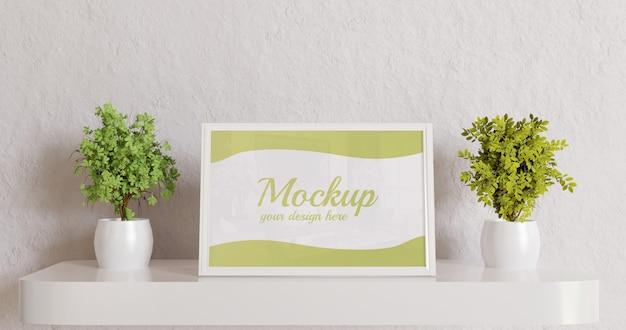Mockup di cornice bianca sulla scrivania a parete con piante di coppia