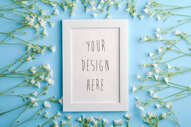 Mockup di cornice per foto vuota bianca con fiori di cerastio su sfondo blu, spazio di copia vista dall'alto