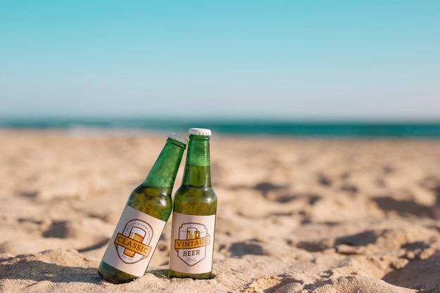 Mockup di due bottiglie di birra in spiaggia