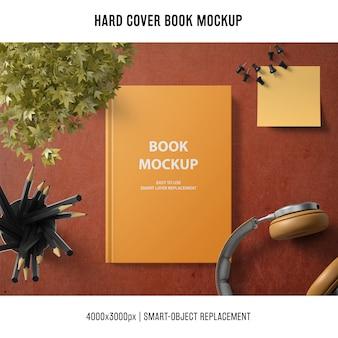 Mockup di libro con copertina rigida con cuffie