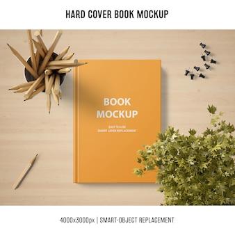 Mockup di libro con copertina rigida con piante e matite
