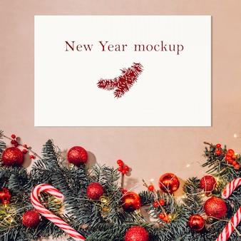 Mockup di natale, cartolina sul tavolo con rami di abete, palline rosse, bacche e bastoncini di zucchero