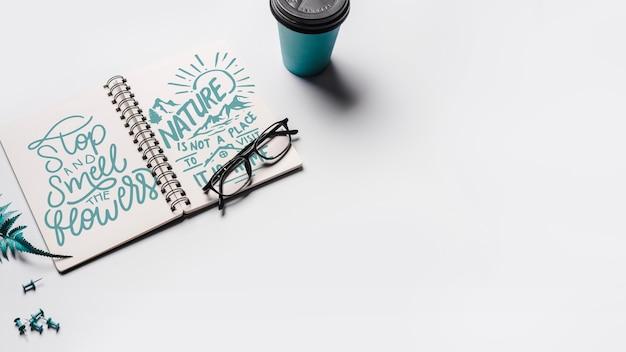 Mockup di notebook con tazza di caffè da asporto