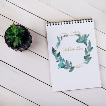 Mockup di notebook primavera con pianta decorativa in vista dall'alto