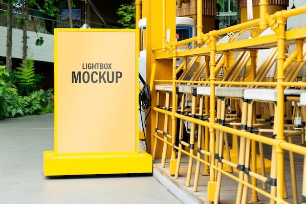 Mockup di scatola di luce gialla in una città per i tuoi contenuti pubblicitari o promozionali.