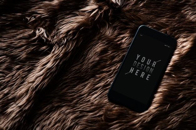 Mockup di schermo del telefono cellulare sulla superficie della pelliccia