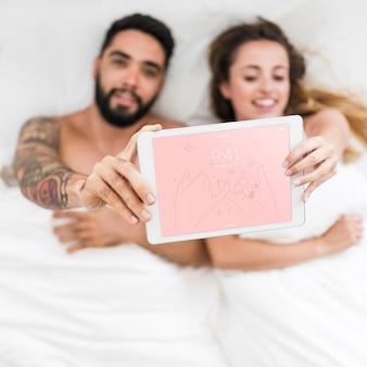 Mockup di tablet con coppia a letto