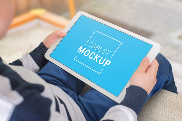 Mockup di tablet nelle mani del bambino. posizione orizzontale. il ragazzo sta sedendosi nel salone e sta guardando il concetto della compressa
