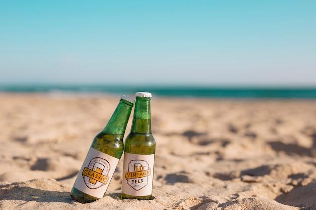 Mockup de dos botellas de cerveza en la playa