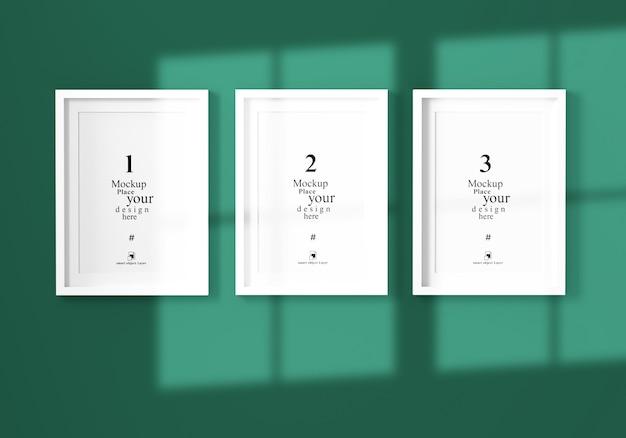 Mockup drie lege fotolijst met schaduw in groene muur, sjabloon psd.