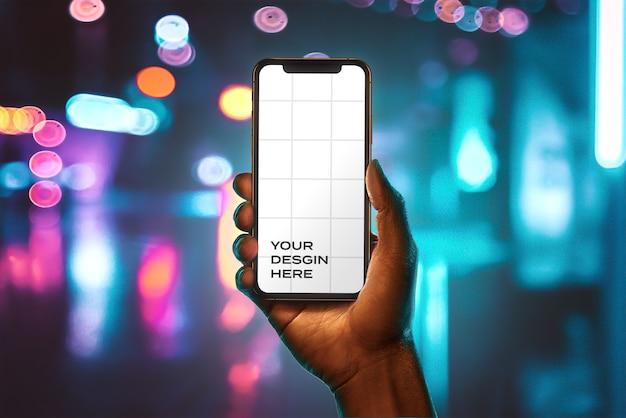 Mockup con efecto bokeh de mano sosteniendo nuevo teléfono inteligente