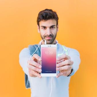 Mockup de fitness con hombre enseñando smartphone