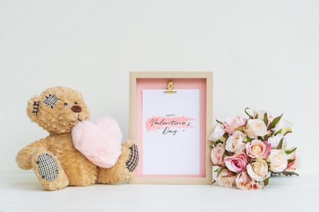 Mockup fotolijst en schattige beer met roze hart en boeket rozen.