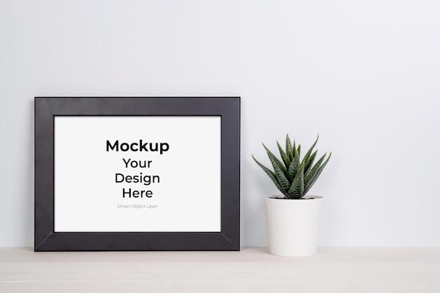 Mockup frame en planten in pot op tafel