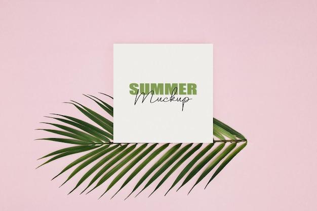 Mockup frame met palmbladeren over roze achtergrond