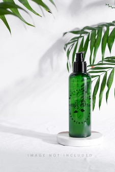 Mockup groene plastic fles met groenblijvende palm tropische bladeren kopieer ruimte