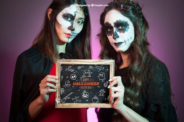 Mockup de halloween con mujeres sujetando pizarras