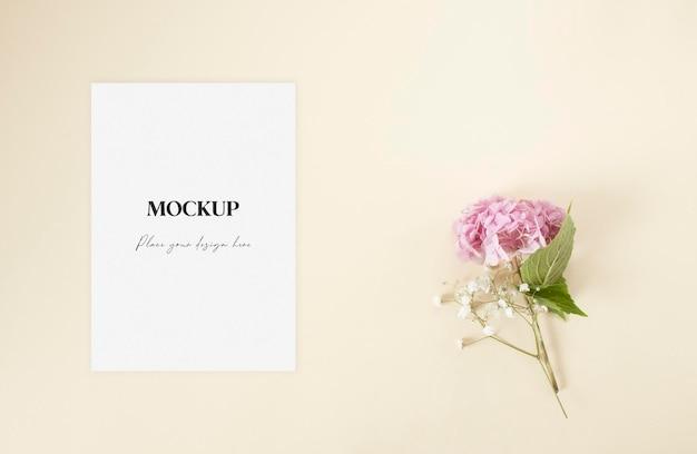 Mockup huwelijksuitnodiging met roze hortensia en gipskruid bloemen op de beige achtergrond
