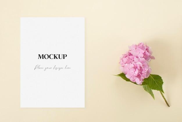 Mockup huwelijksuitnodiging met roze hortensia op de beige achtergrond
