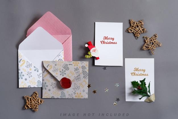 Mockup-kerstkaarten met enveloppen en vakantiedecoratie.