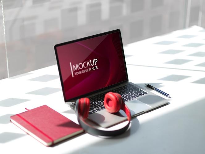 Mockup-laptop met hoofdtelefoon en notitieboekje