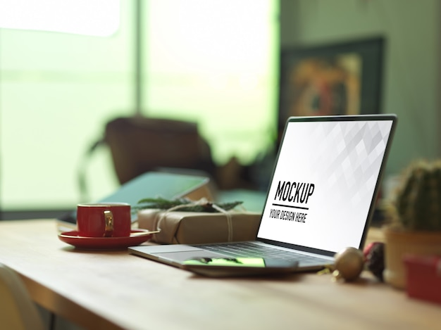 Mockup laptop op houten tafel met smartphone