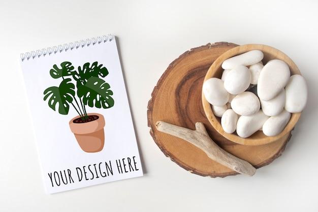 Mockup lege notebook lijst met een kom met witte kiezelsteen en boho rustieke decoraties op een witte tafel.