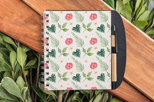 Mockup de libreta con hojas tropicales