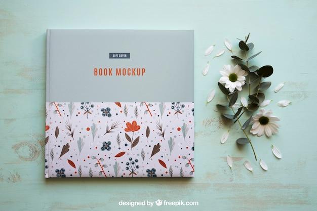 Mockup de libro al lado de flores