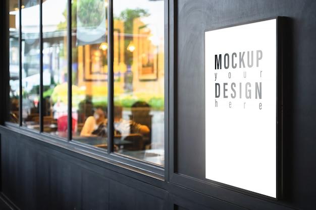 Mockup lightbox op de zwarte muur met vage restaurantachtergrond.